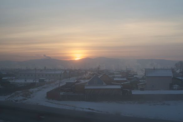 Wood smoke rises to greet the sun who finally peeps over the hills at 10:00 am.