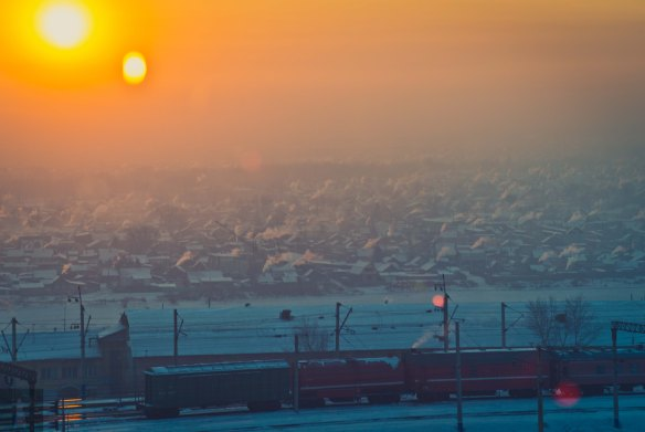 Looking west over the Trans-Siberian Railway toward the left bank of the Selenga. The people of Sovietski region stoke their stoves against the approach of a frigid eve.