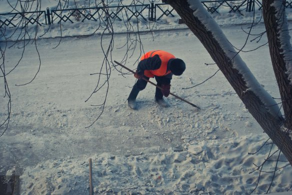 Our neighborhood maintenance worker chipping away packed snow along the driveway under our apartment building.