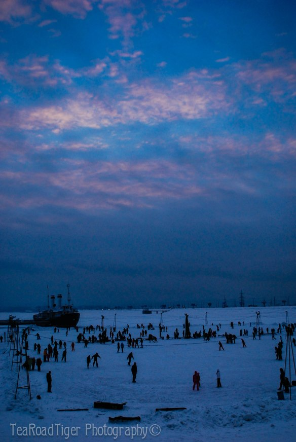 "Ice skaters revel in the chill, next to the historical icebreaker ""Angara"" on the Angara river, Irkutsk."