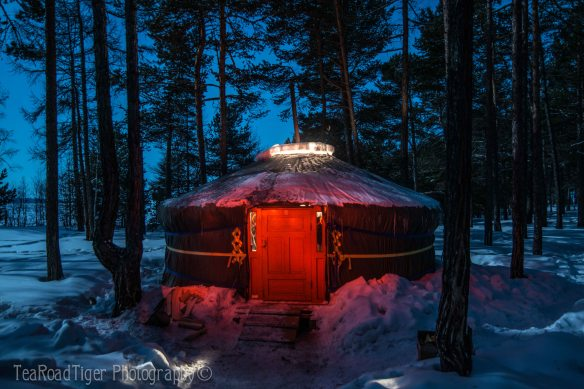 Glowing winter yurt on Lake Baikal's shore.