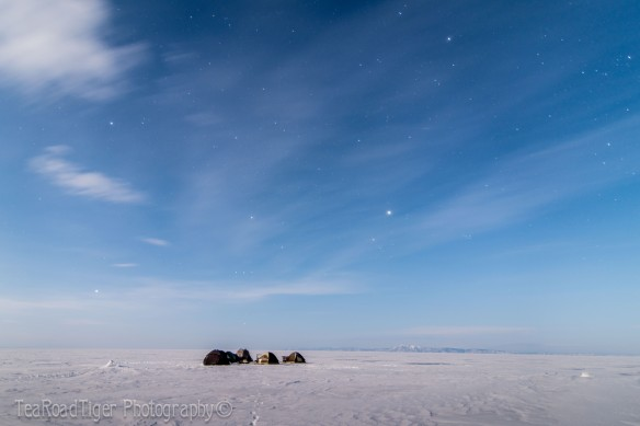 Clouds and stars compete over the vast frozen basin of Lake Baikal in March. Yes, one of those tents is mine!