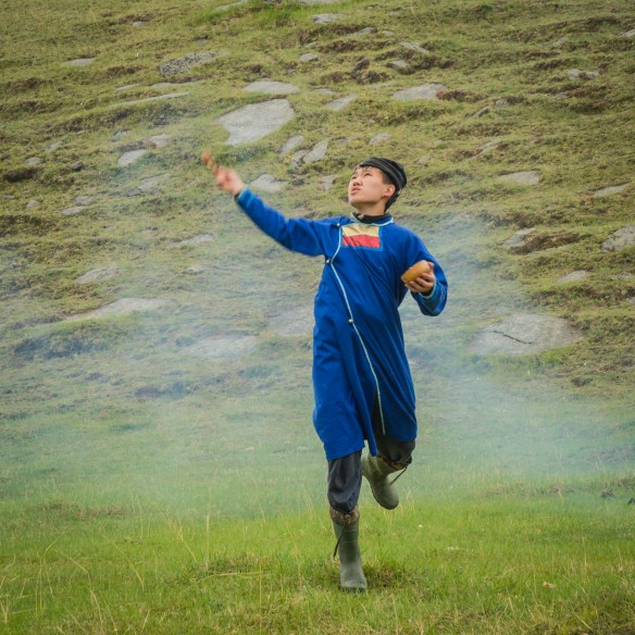 A young Buryat shaman flings an oblation of milk during opening of the Yordinkski games on the shores of Lake Baikal.