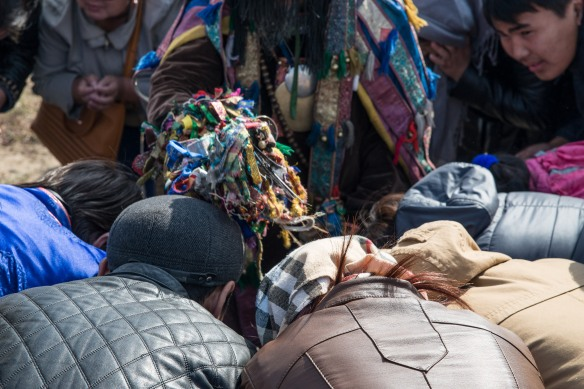 People bow before a shaman as she bestows blessings.